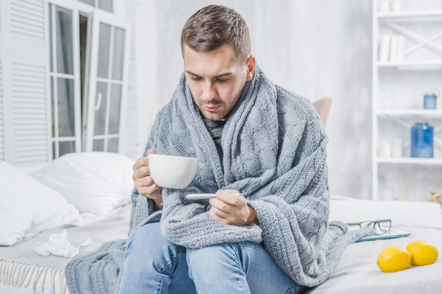 sick-man-sitting-bed-holding-cup-coffee-checking-fever-thermometer_23-2147948517