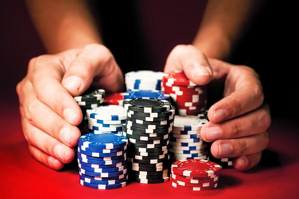 Man's hands move the winnings casino chips on red table.